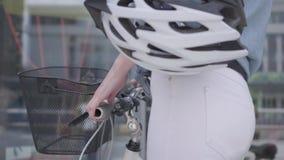 带领她的自行车的白色牛仔裤的未被认出的年轻亭亭玉立的可爱的白肤金发的妇女在商店窗口附近在城市 ?treadled 股票录像