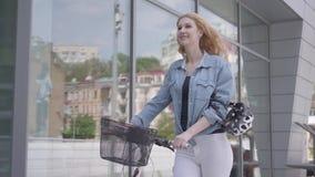 带领她的自行车的白色牛仔裤的画象逗人喜爱的年轻亭亭玉立的可爱的白肤金发的妇女在商店窗口附近在城市 股票视频