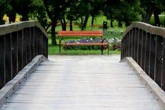 带领往木公园长凳的葡萄酒减速火箭的浪漫老木桥有金属支持围拢与花和 库存照片
