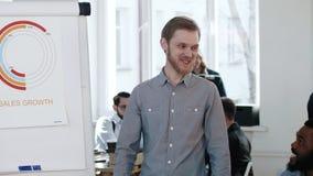 带领现代办公室研讨会的年轻活跃微笑的欧洲企业辅导者人,解释销售在flipchart用图解法表示 影视素材