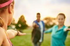带领瑜伽类的年轻白肤金发的妇女在日落在自然公园 免版税图库摄影