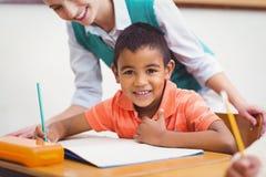 帮助一个小男孩的老师在类期间 免版税库存照片
