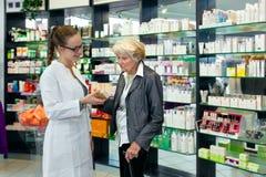 帮助一个资深夫人的药剂师 免版税库存图片