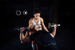 帮助一个年轻人的女性个人健身辅导员在健身房 库存照片