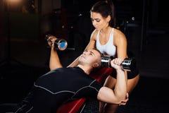 帮助一个年轻人的女性个人健身辅导员在健身房 库存图片
