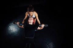 帮助一个年轻人的女性个人健身辅导员在健身房 免版税库存照片
