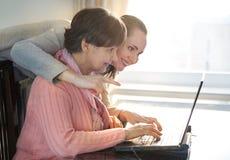 帮助一个年长人的少妇使用便携式计算机为互联网查寻 年轻人和工作toget的退休金使用年限世代 免版税库存照片