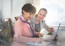 帮助一个年长人的少妇使用便携式计算机为互联网查寻 年轻人和工作toget的退休金使用年限世代 库存照片