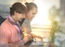 帮助一个年长人的少妇使用便携式计算机为互联网查寻 图库摄影