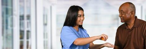 帮助一个年长人的护士采取药片 图库摄影