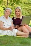帮助一个年长用途的少妇膝上型计算机 免版税库存图片