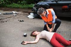 帮助一少妇说谎的一个人不自觉在路在车祸以后 免版税图库摄影