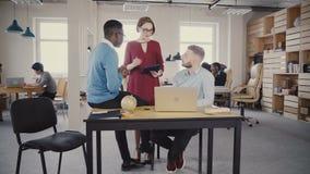 帮助不同种族的同事的友好的女性经理 女队领导显示关于片剂的新的数据给办公室工作者4K 股票录像