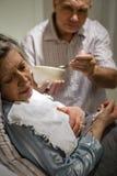 帮助不适的妻子哺养的汤的成熟人 库存照片