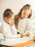 帮助与家庭作业的更老的姐妹画象到更加年轻一个 免版税图库摄影