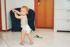 帮助与清洁的可爱的1岁男婴 免版税库存照片