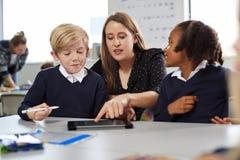 帮助两个孩子的女性学校老师使用片剂计算机在书桌在一间小学教室,正面图 免版税库存图片