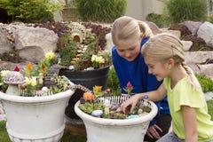 帮助两个的女孩做花盆的神仙的庭院 免版税库存照片