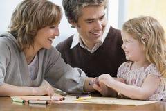 帮助他们的女儿的父母画 免版税图库摄影
