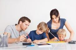 帮助他们的有家庭作业的父项子项 库存图片