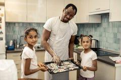 帮助他们的父亲的女儿放曲奇饼入烤箱 免版税库存图片