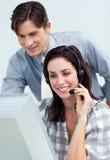 帮助他微笑的生意人同事 免版税库存图片