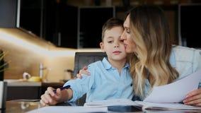 帮助他的儿子的微笑的母亲做家庭作业,命令文本帮助您写坐在桌上在厨房 股票录像