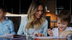 帮助他的儿子的微笑的母亲做家庭作业,命令文本帮助您写坐在桌上在厨房 股票视频