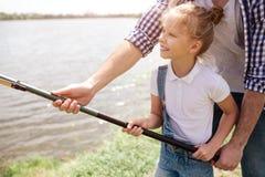 帮助他的女儿的人的图片拿着鱼标尺用一个正确的方式 女孩举行它用两手和微笑 库存照片
