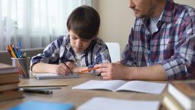 帮助他的小儿子的有同情心的父亲做家庭作业,爸爸支持,教育 股票视频