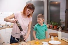 帮助他的有烹调的小男孩母亲在厨房里 库存图片