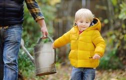 帮助他的父亲水厂的逗人喜爱的小孩男孩 免版税图库摄影