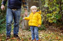 帮助他的父亲水厂的逗人喜爱的男孩在庭院里 免版税库存照片