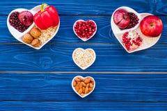 帮助健康心脏的逗留的食物 菜,果子,在心形的碗的坚果在蓝色木背景顶视图 库存照片