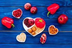 帮助健康心脏的逗留的食物 菜,果子,在心形的碗的坚果在蓝色木背景顶视图 图库摄影