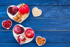 帮助健康心脏的逗留的食物 菜,果子,在心形的碗的坚果在蓝色木背景顶视图 库存图片