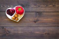 帮助健康心脏的逗留的食物 菜,果子,在心形的碗的坚果在黑暗的木背景顶视图 库存图片