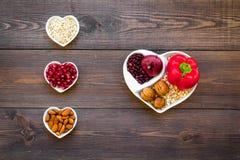 帮助健康心脏的逗留的食物 菜,果子,在心形的碗的坚果在黑暗的木背景顶视图 库存照片