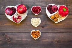 帮助健康心脏的逗留的食物 菜,果子,在心形的碗的坚果在黑暗的木背景顶视图 免版税库存图片