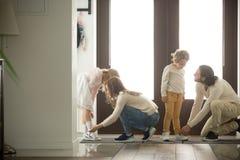 帮助儿子和女儿的父母在家投入了鞋子  免版税库存图片