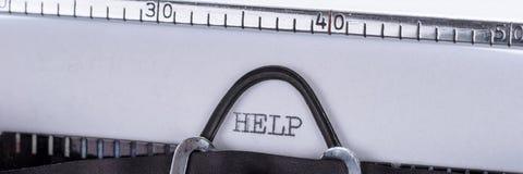 帮助写与贷方在一台老打字机 图库摄影