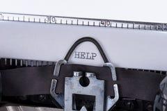 帮助写与贷方在一台老打字机 库存图片
