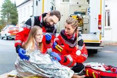 帮助受伤的妇女的救护车医生 免版税库存图片