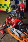帮助受伤的摩托车驾驶员的紧急队 免版税库存图片
