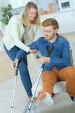 帮助受伤的男朋友的妇女 免版税库存照片