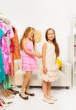 帮助另一个的女孩通过适合礼服 免版税图库摄影