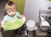 帮助在厨房里的可爱的微笑的白肤金发的小孩男孩采取板材在盘洗衣机外面 免版税图库摄影