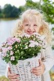 帮助在庭院里的白肤金发的女孩 免版税库存照片