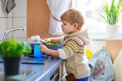 帮助在有洗涤的盘的厨房里的小小孩 免版税库存图片