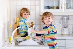 帮助在有洗涤的盘的厨房里的滑稽的双男孩 免版税库存照片